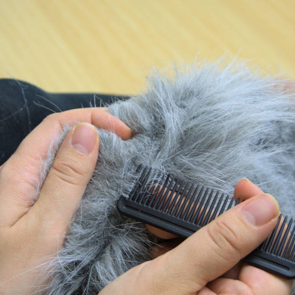 Using a comb to pull out faux fur stuck in seams.