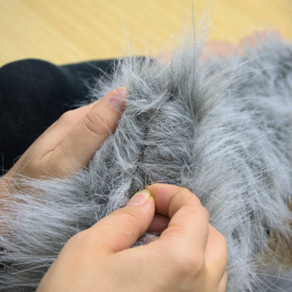 Using a pin to pull out faux fur stuck in seams.
