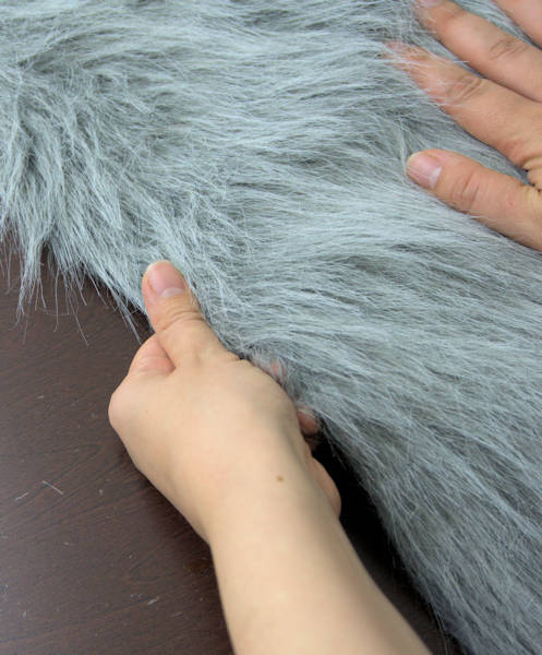 Running hand along cut edge to remove loose fur.