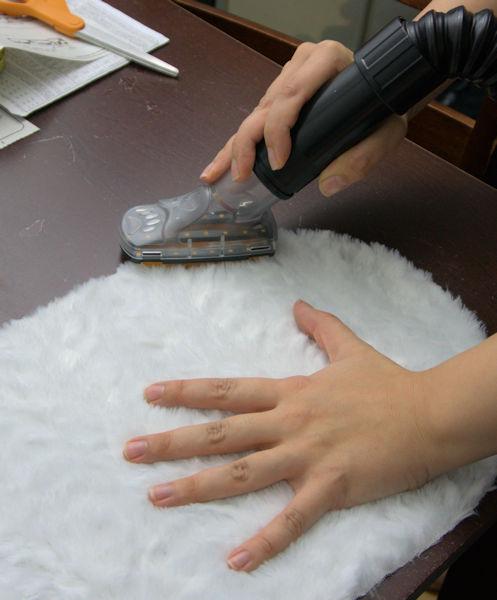 Vacuuming faux fur cut edge.