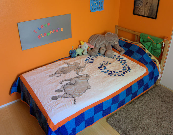 Elephant quilt on my kid's bed along with several stuffed animals