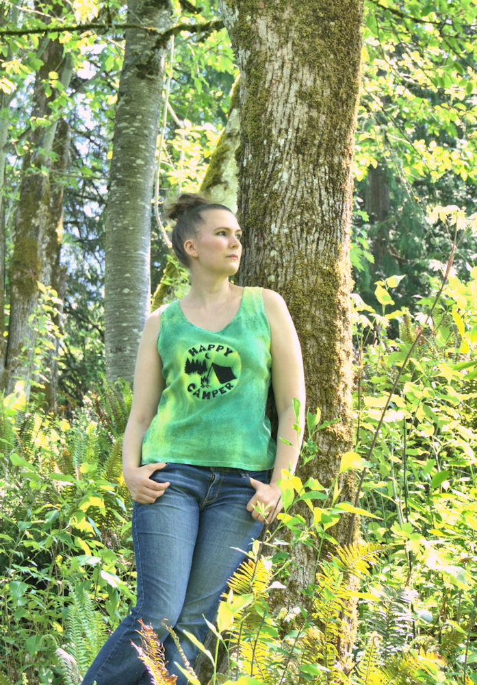 "Wearing ""Happy Camper"" tank top while leaning against a tree"