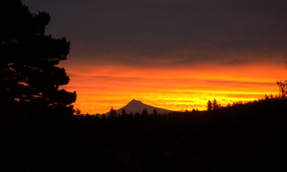 Mt. Hood at sunrise, with yellows, oranges, reds and purples in the sky