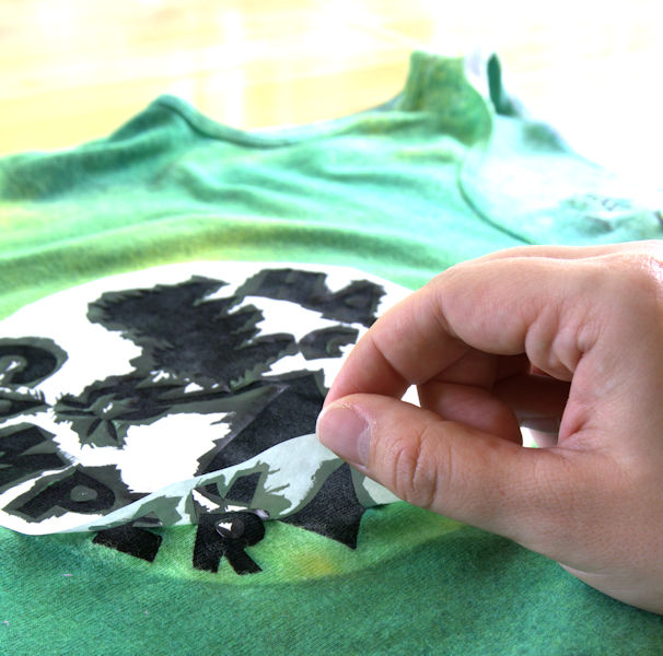 Carefully peeling the stencil away from the shirt