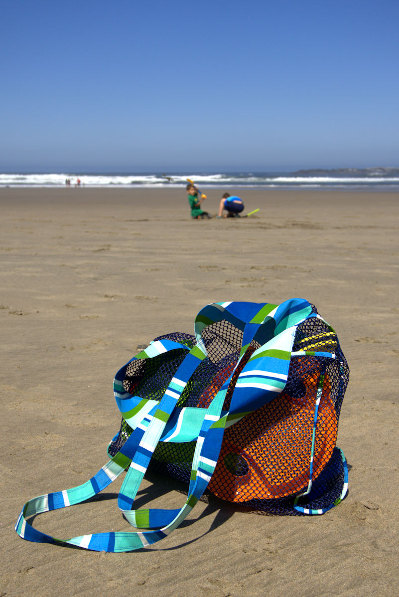 Mesh beach toy bag sitting on the beach with children playing in background