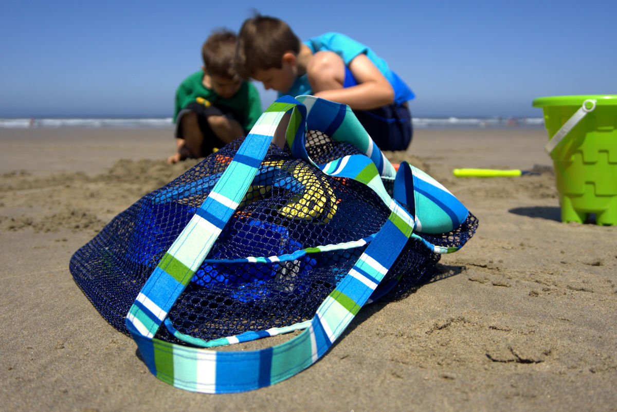Mesh beach toy bag sitting on beach with kids digging in background
