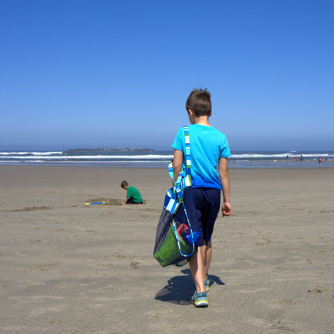 Kid walking on the beach with mesh toy bag over his shoulder
