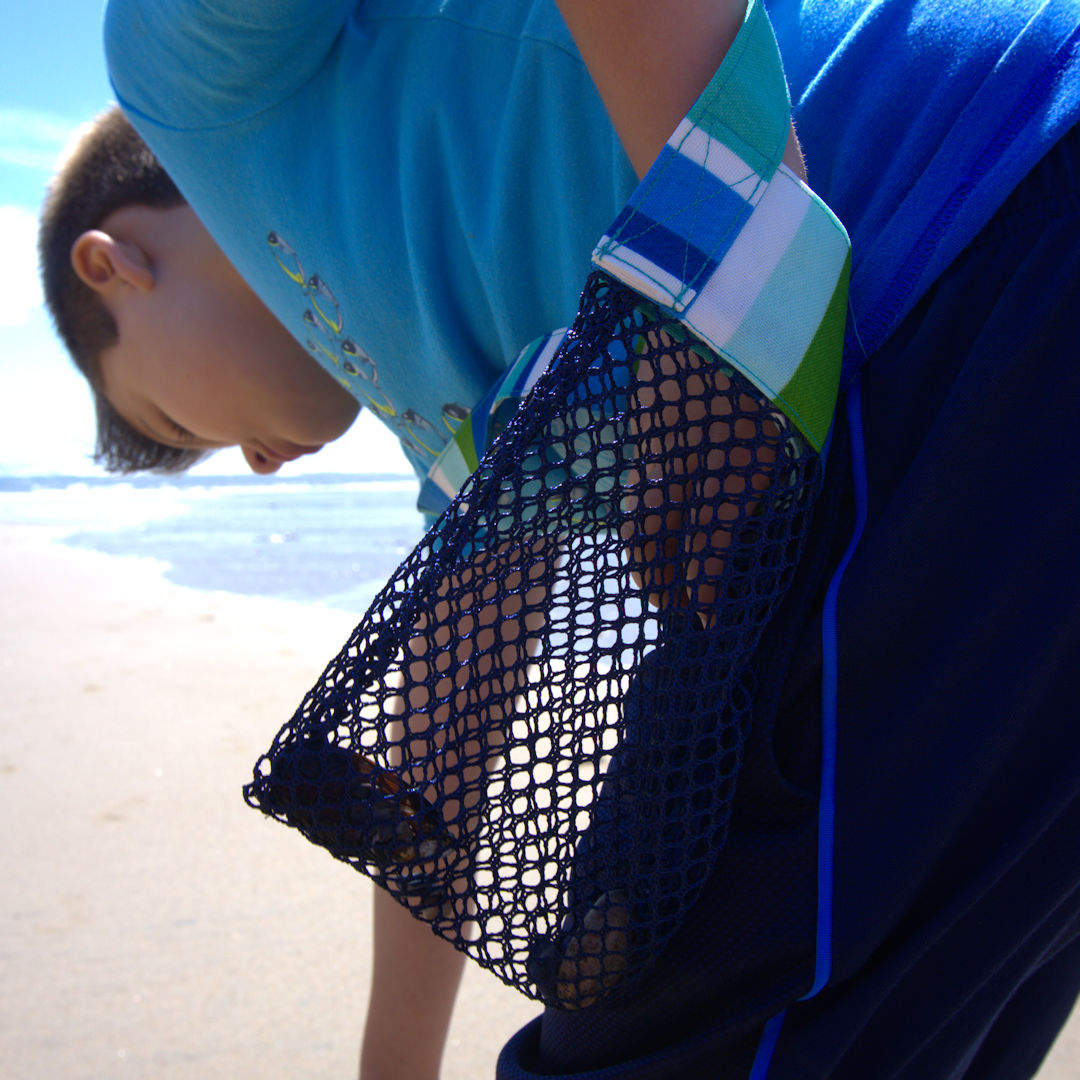 Boy collecting seashells with mesh bag
