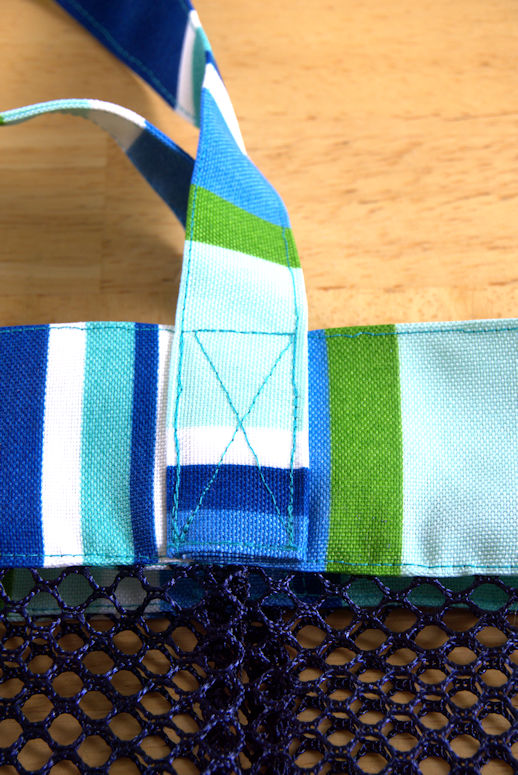 Strap attached to the bag by stitching an X