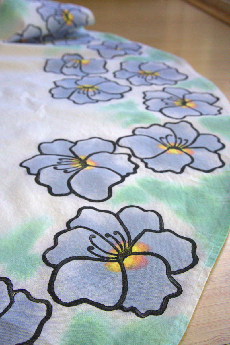 Black out lined dusky blue painted flowers around green watercolor paint