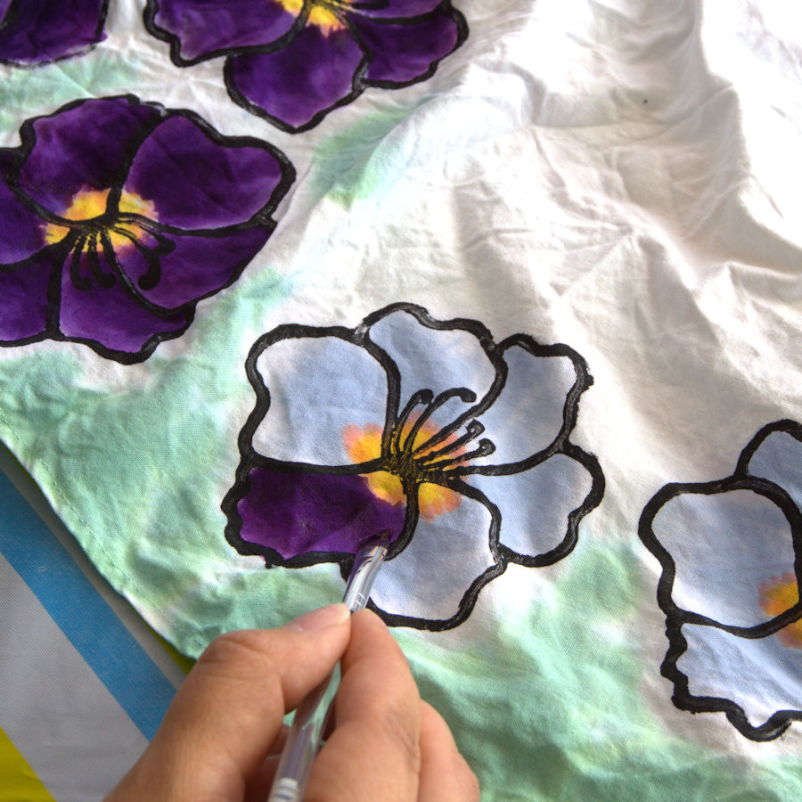 Painting purple dye on flower on fabric