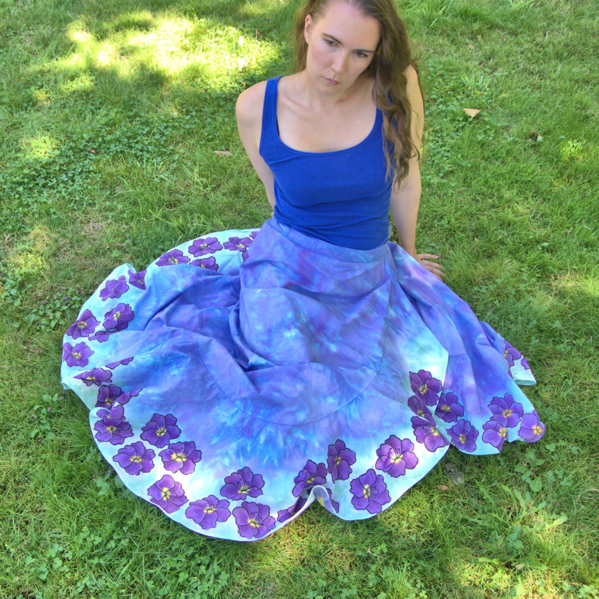 Sitting on ground with purple-blue wrap skirt displaying purple flowers