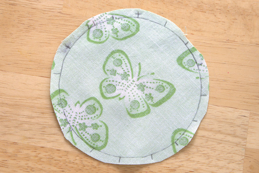 Circle cut with seam allowance from green butterfly fabric
