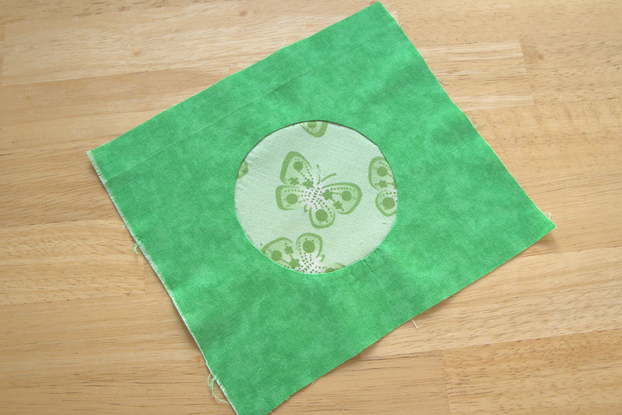Butterfly fabric circle sewn inset into green fabric