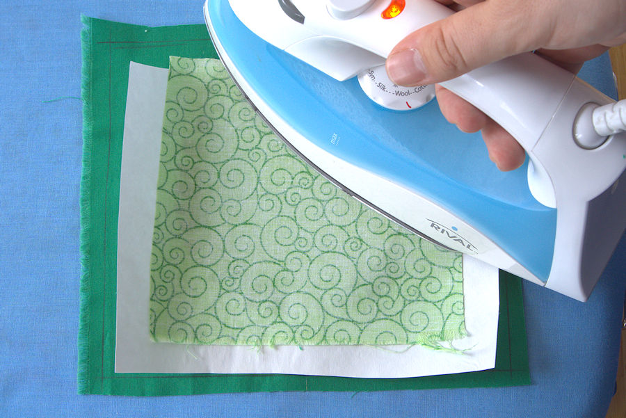 Ironing the layers of fabric and freezer paper