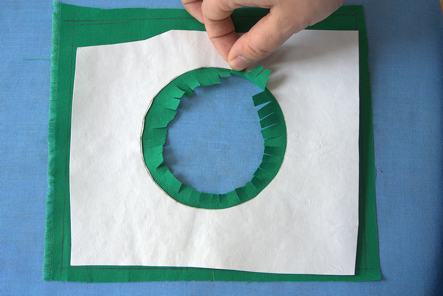Fringes cut into the seam allowance of green fabric