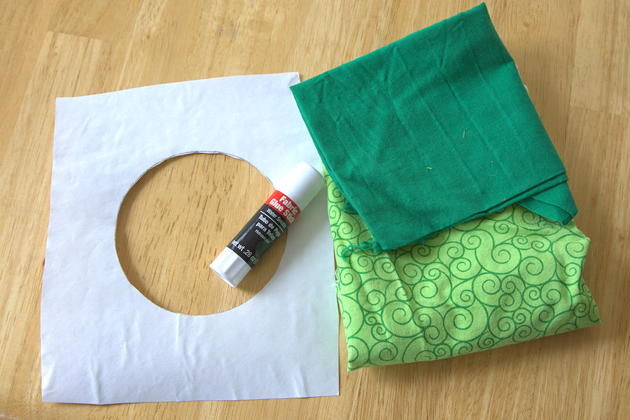 Freezer paper, washable glue stick, and two pieces of green fabric