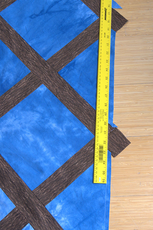 Extending the line on the quilt using a yardstick