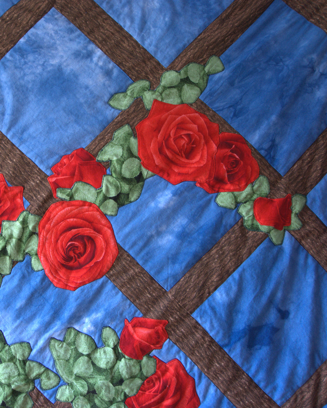 Closeup of applique flowers on lattice quilt