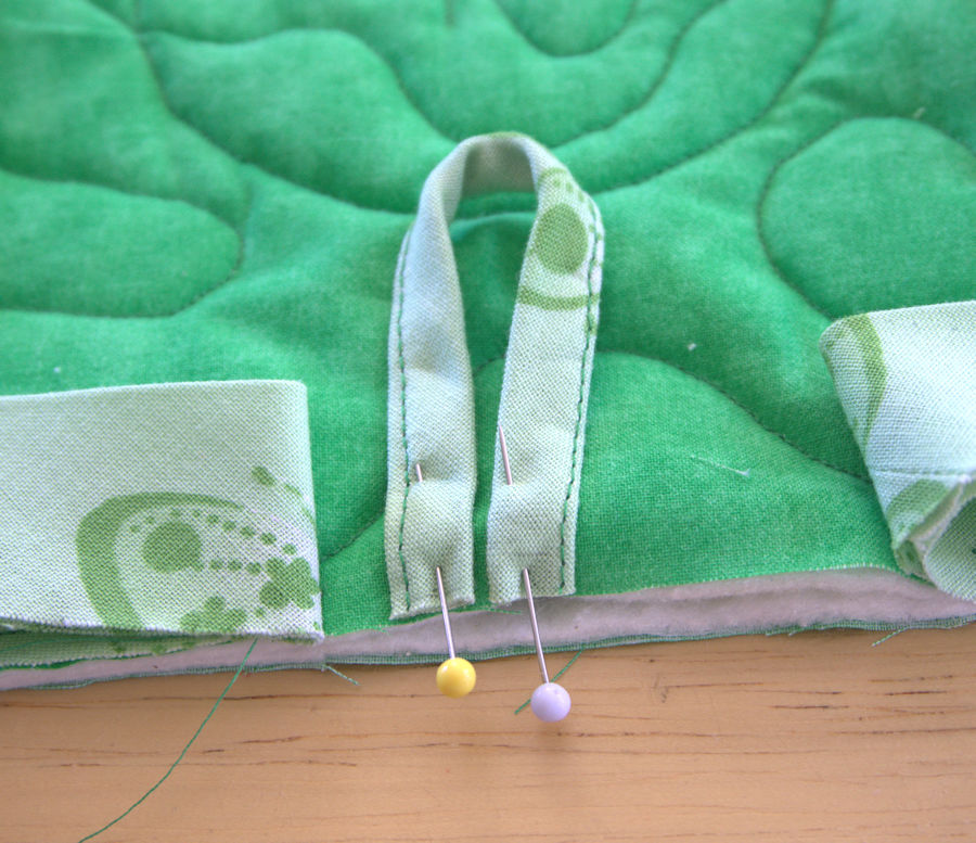 Green fabric loop pinned to potholder