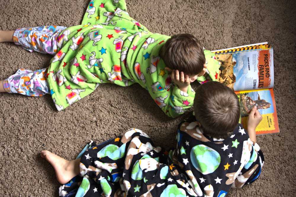 Boys in robes reading book