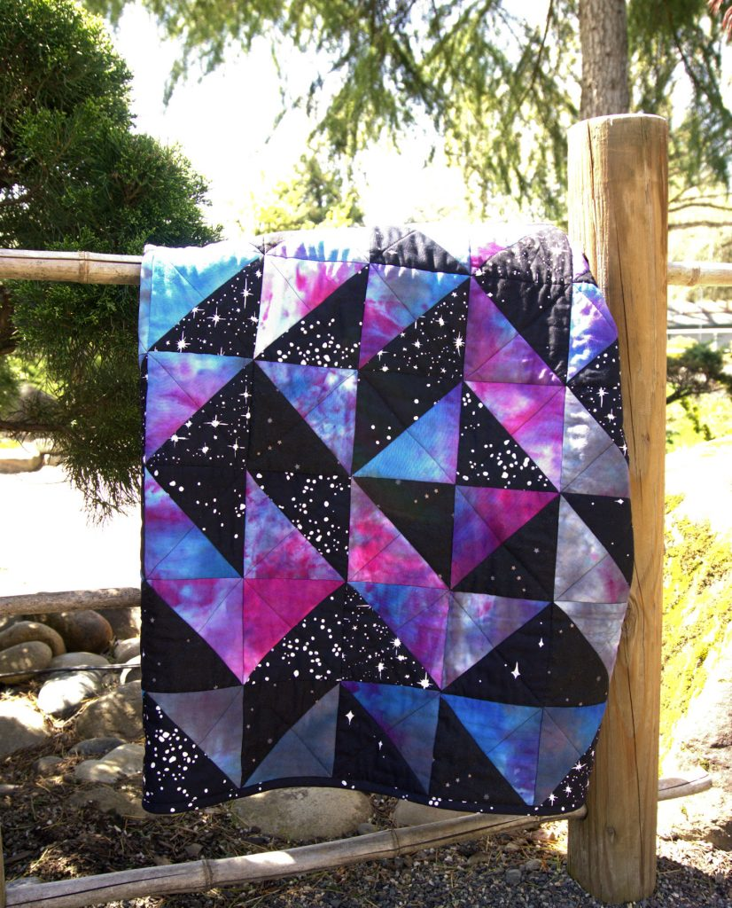 Folded galaxy half square triangle quilt