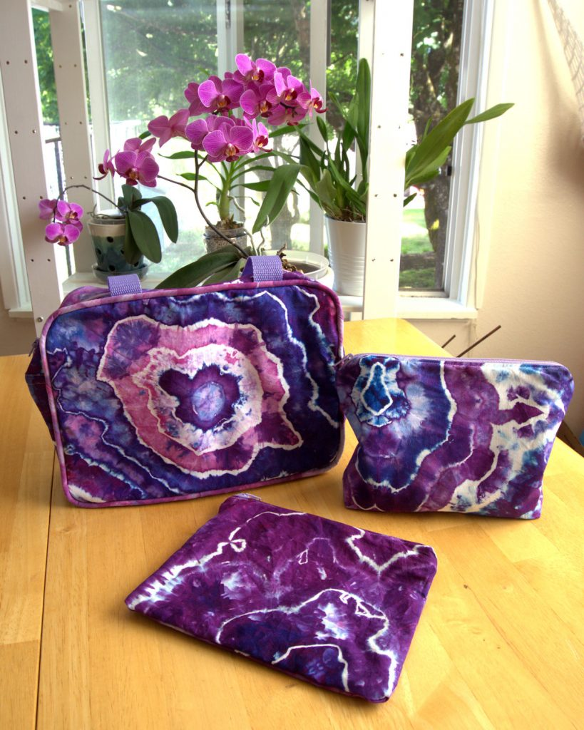 Three travel accessory bags made from geode fabric