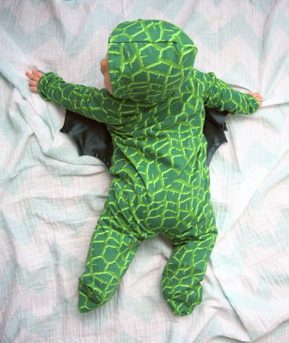Baby in green winged dragon pajamas