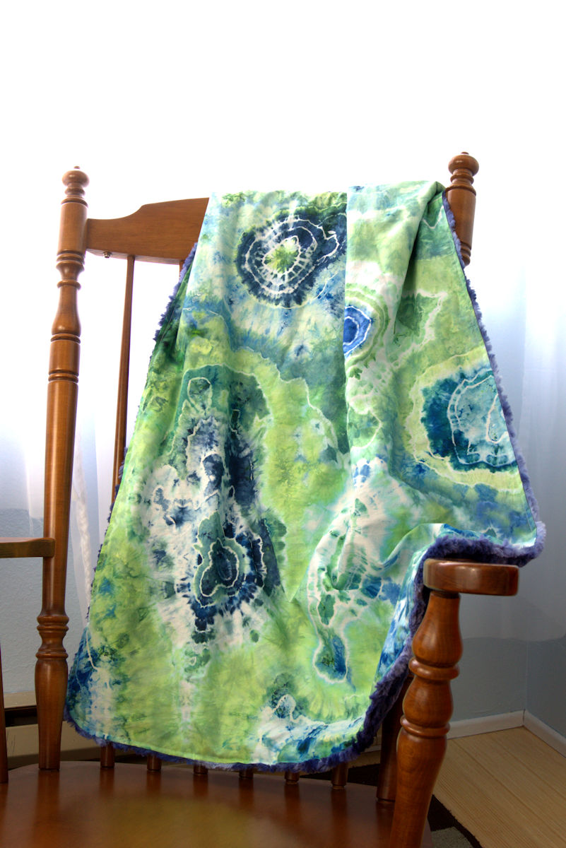 Minky blue and green geode baby blanket on rocking chair