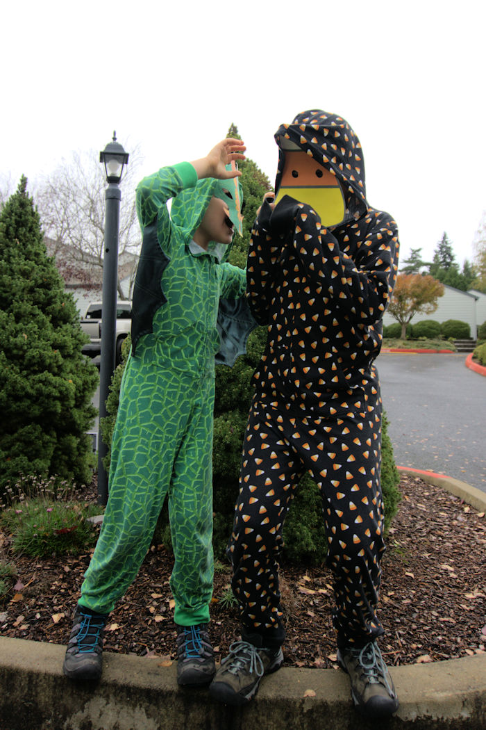 Kid in dragon pjs scaring brother in candy corn pjs