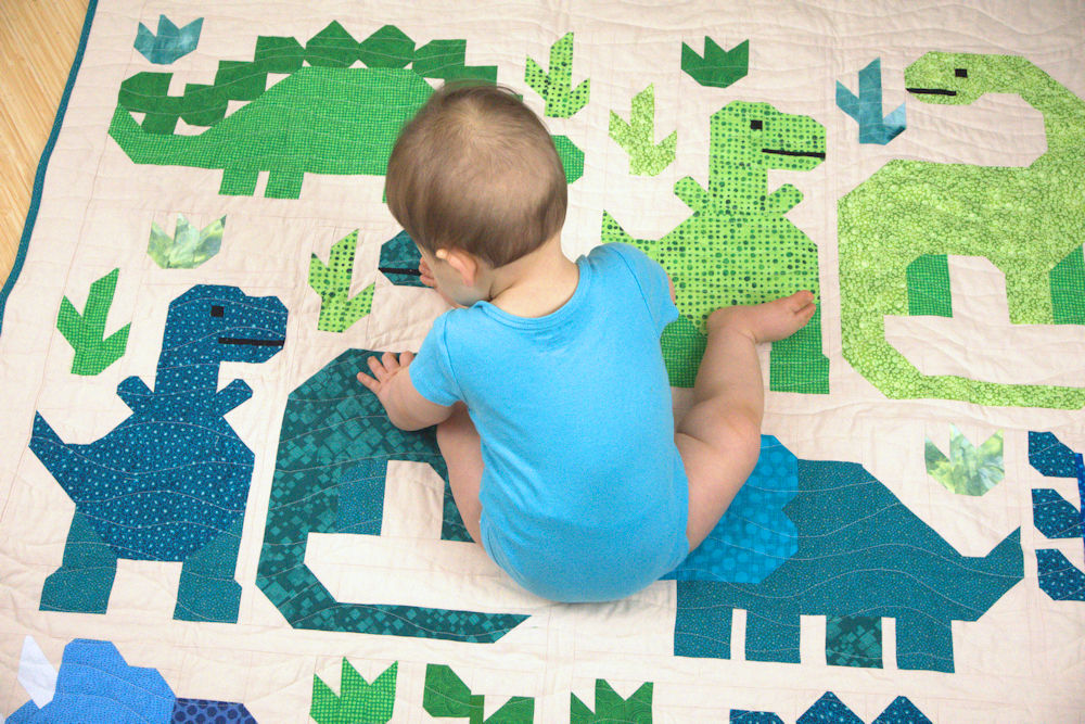 Baby sitting on Elizabeth Hartman's Dinosaur Sampler Quilt
