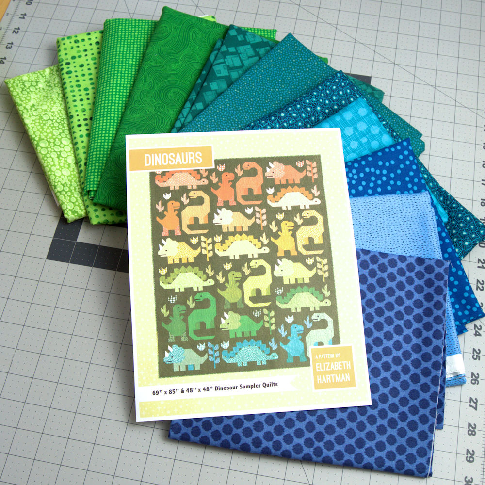 Fabric choices in ranges from blue to green for Dinosaurs quilt