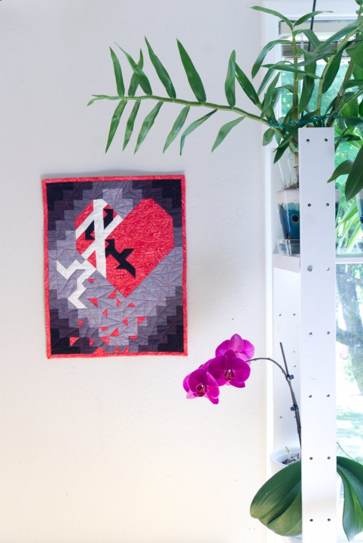 Broken heart mini quilt hanging on wall next to orchids