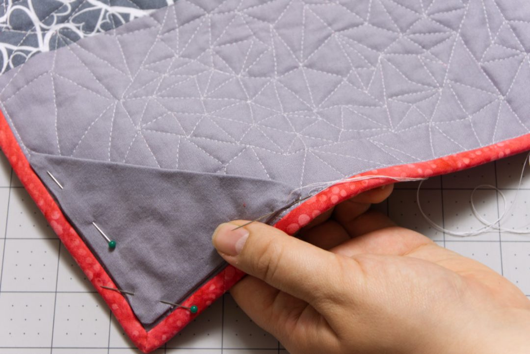 Hand sewing pockets on back of mini quilt