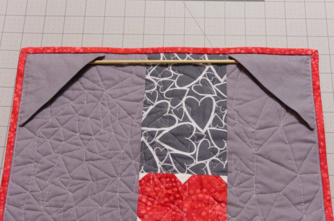 Wooden rod on back of mini quilt