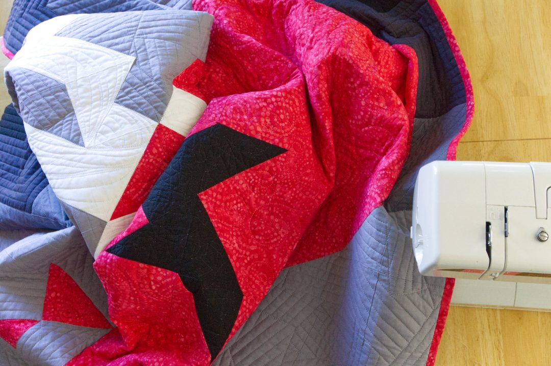 Sewing binding on pink and gray quilt