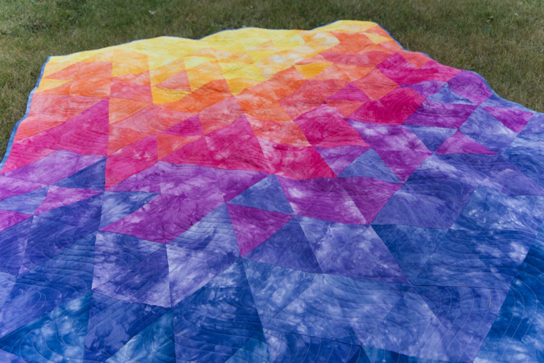 Blue, purple, pink, orange and yellow gradient quilt