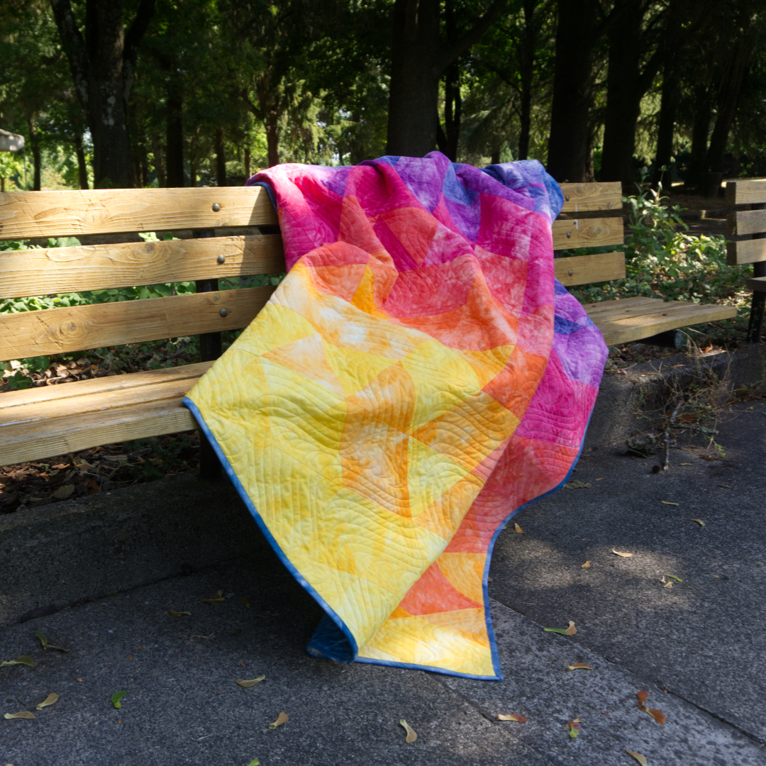 Yellow, pink, and blue gradient quilt on bench