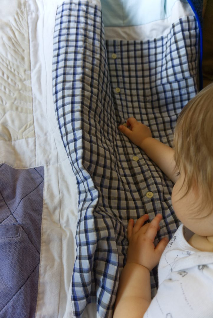 Toddler playing with buttons on quilted shirt